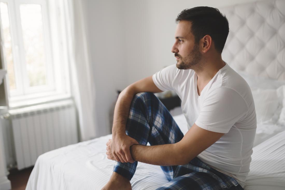 Homem sentado em uma cama olhando contemplativa, sofrendo de disfunção erétil, ou ed.