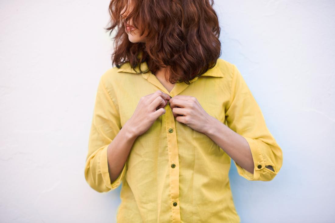 髪の毛の乳首を隠すために彼女のシャツを押し上げている女性。