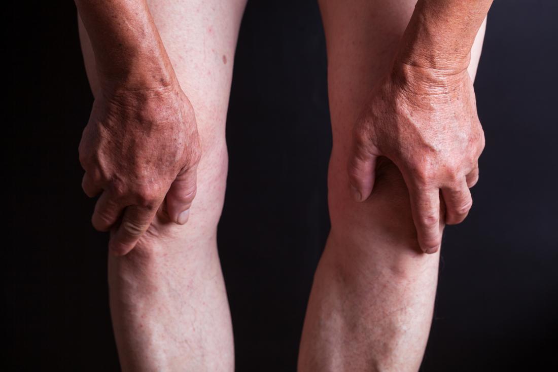両膝を持つ高齢者