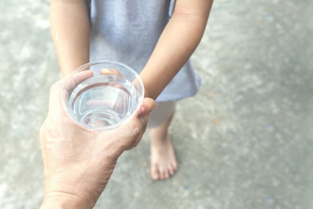 Adulte donnant une tasse d'eau à l'enfant pour rester hydraté.