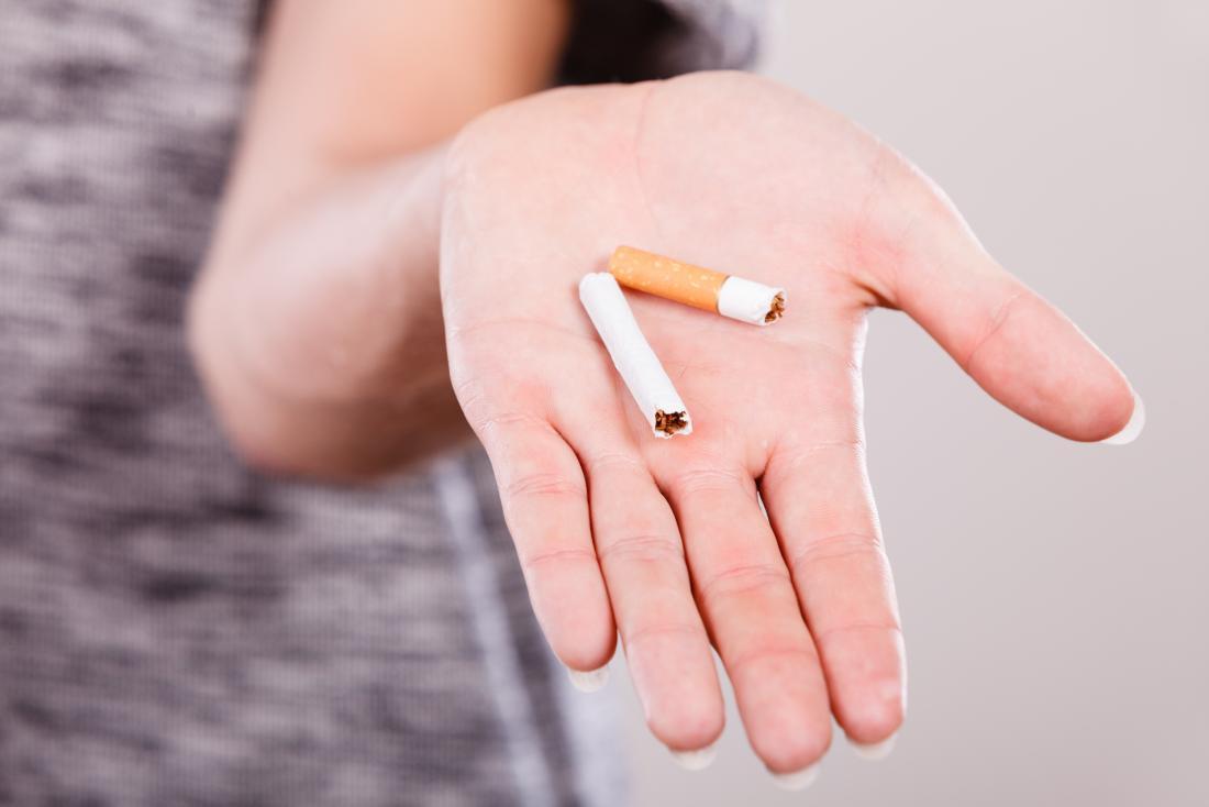 femme montre une cigarette cassée. Cesser de fumer peut aider avec les ulcères de la gorge