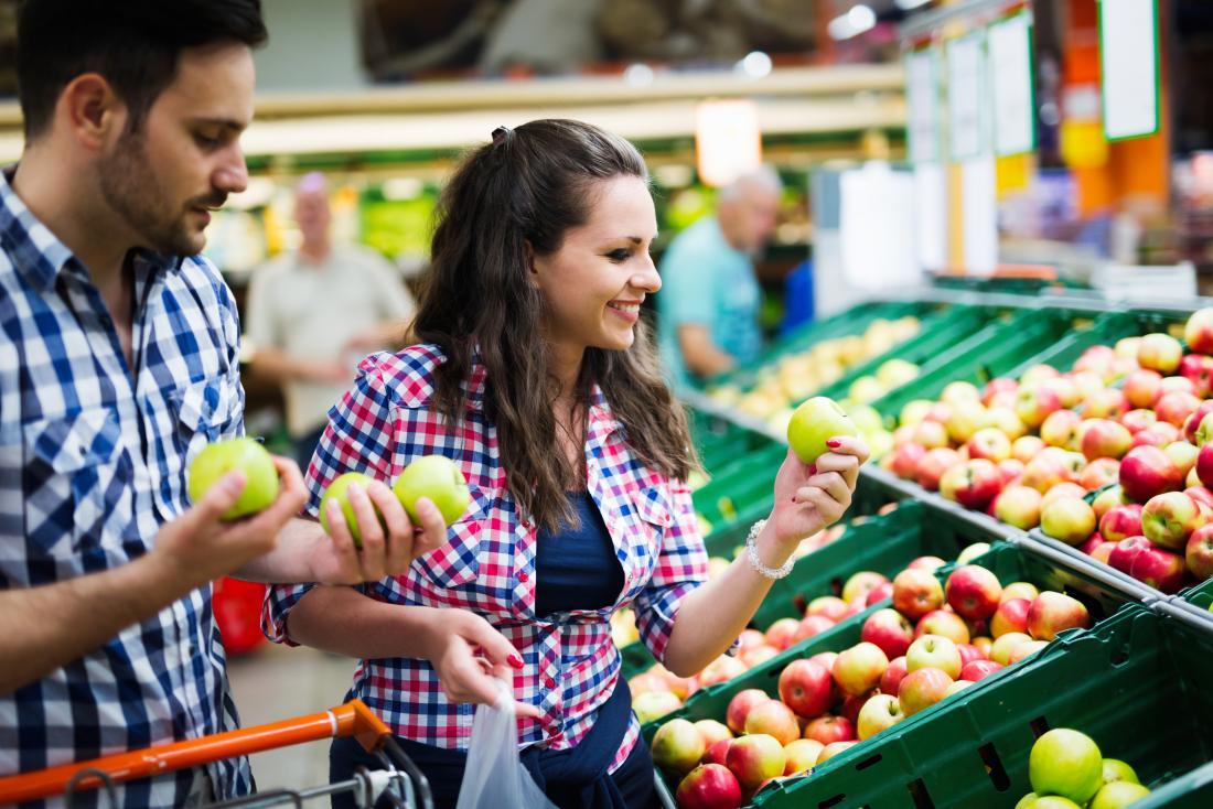 Homme et femme shopping pour les fruits et légumes en supermarché.