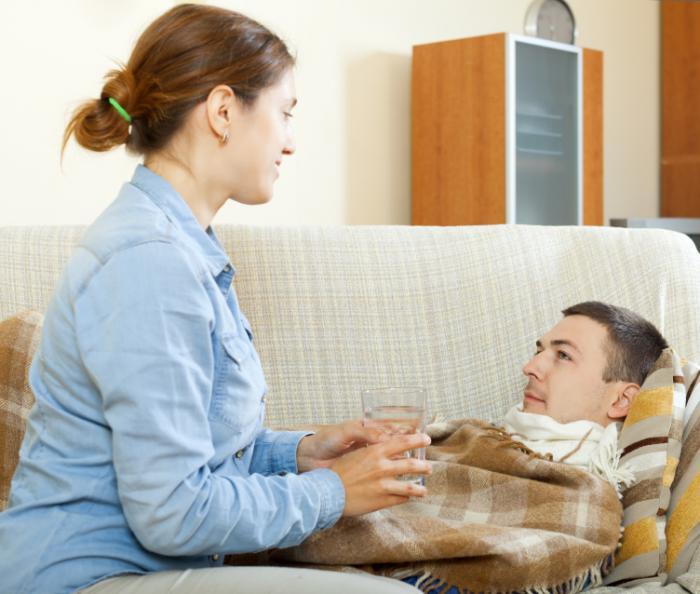 Uma mulher dá um copo de água para um homem em um sofá.