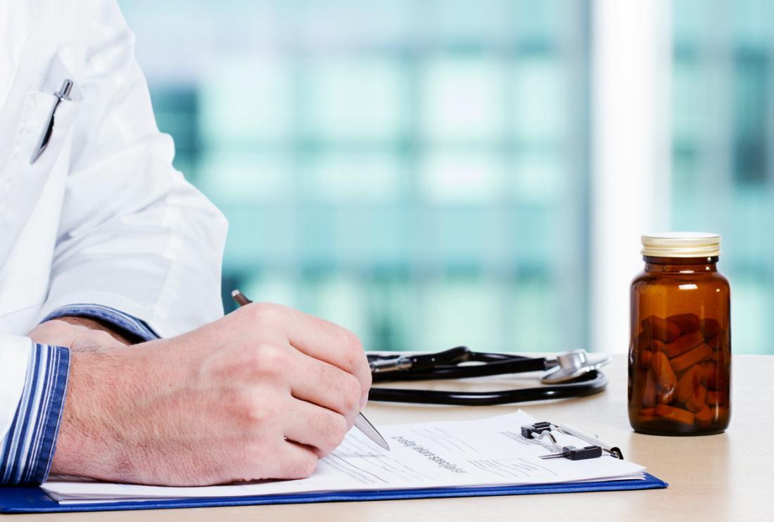 Docteur écrit des notes avec des pilules sur le bureau