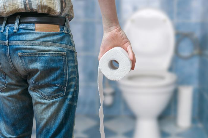 トイレットペーパーを手にしてトイレに向かう男