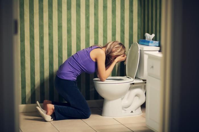 Senhora doente no vômito do banheiro
