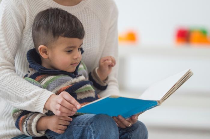 Kleiner Junge mit seiner Mutter lesen