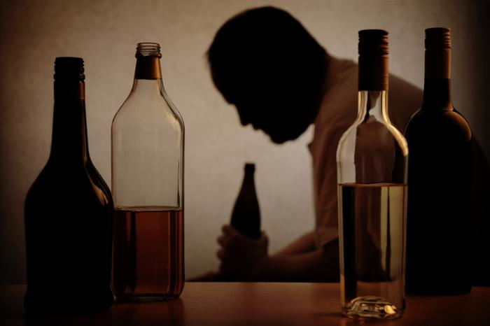 Um homem senta-se amamentando uma garrafa de álcool. Em primeiro plano estão 4 garrafas diferentes de álcool