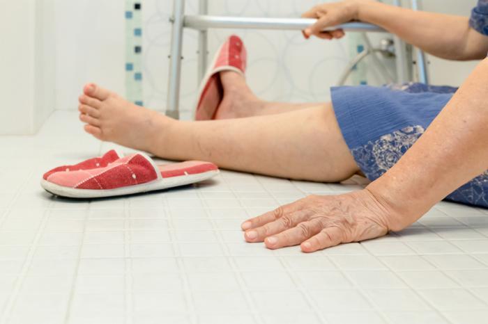 la signora è seduta sul pavimento del bagno con la cornice zimmer dopo una caduta