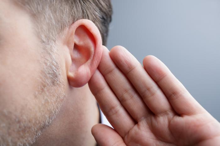 Hand hinter dem Ohr versucht zu hören