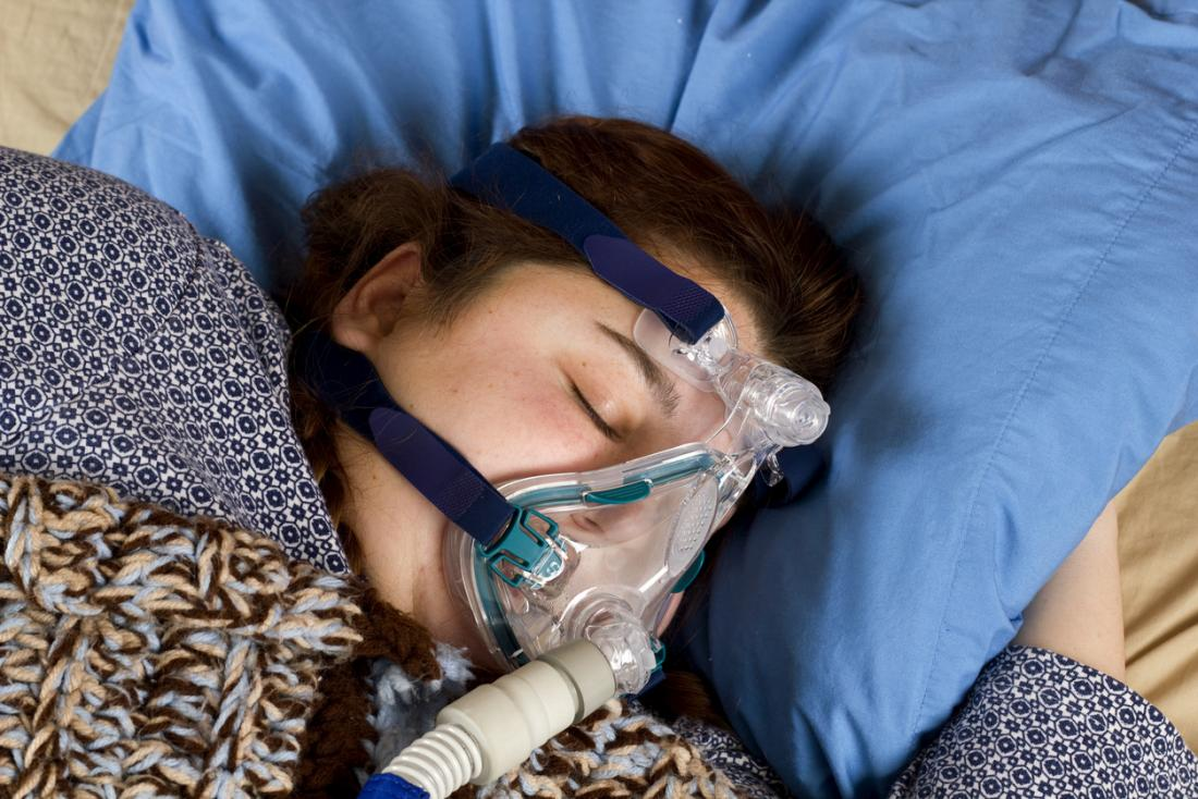 [Femme portant un masque à pression positive continue des voies respiratoires]