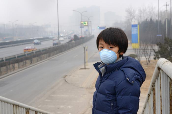 tragende Maske des jungen Jungen in einer Stadt gefüllt mit Smog