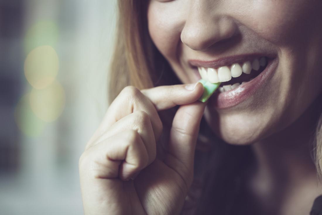 senhora colocando um pedaço de goma de mascar na boca dela