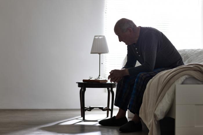 Velho sentado no sofá olhando desanimado
