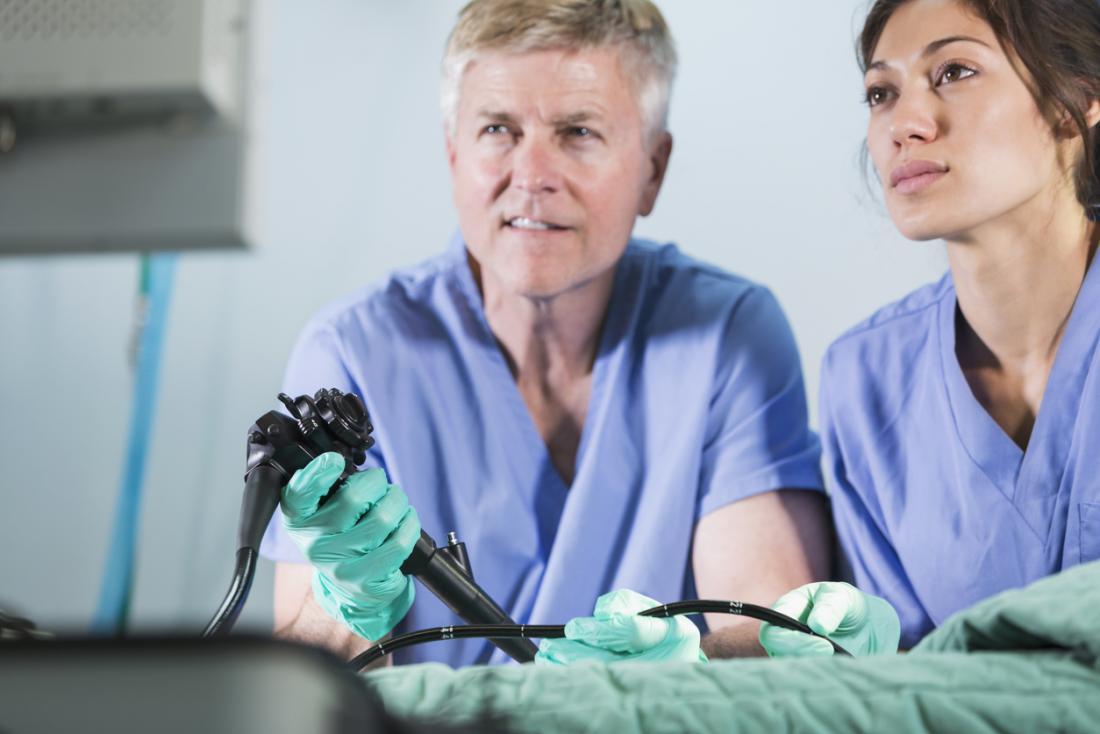 Двама хирурзи гледат монитора докато се извършва ендоскопия.