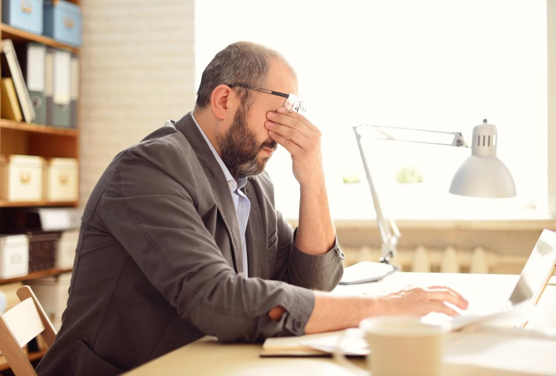 Homem sentado na mesa, esfregando os olhos, estressado e com uma dor de cabeça.