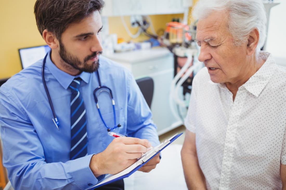 Jeune homme médecin avec un presse-papiers en consultation avec un patient âgé.