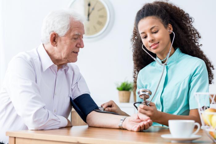 Um homem mais velho está tendo sua pressão sanguínea medida por uma mulher.