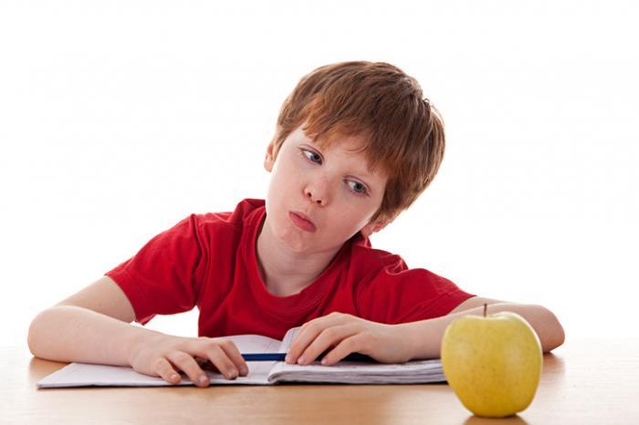 Um jovem rapaz é distraído por uma maçã.