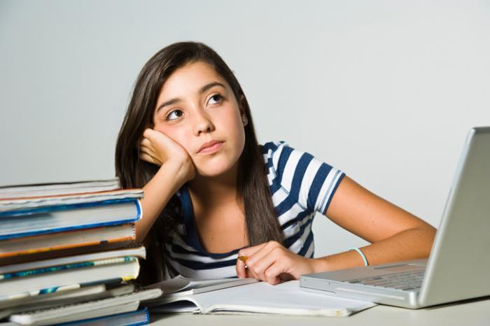 Uma garota está distraída de estudar.