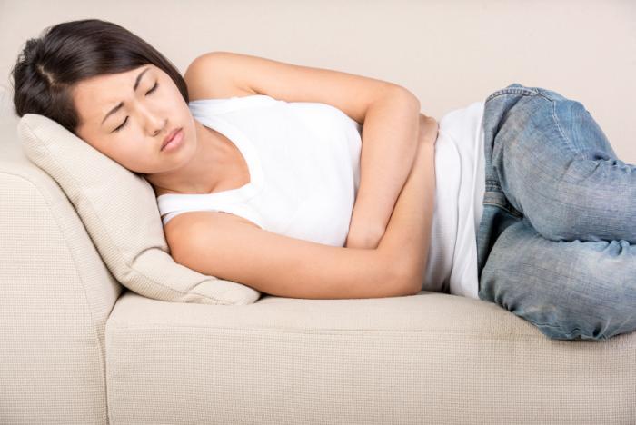 Жена на дивана, която държи корема си в дискомфорт.