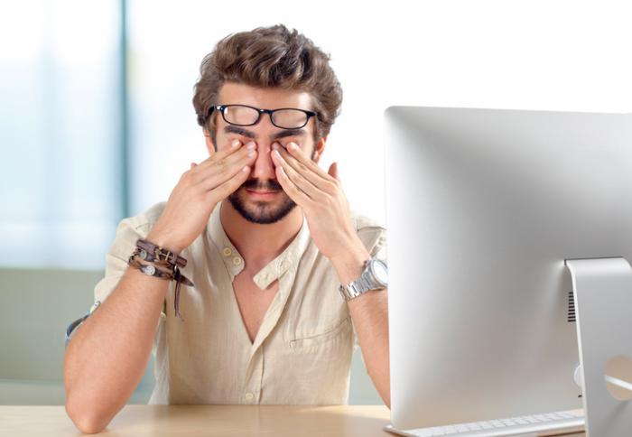[Jeune homme frottant les yeux devant l'ordinateur]