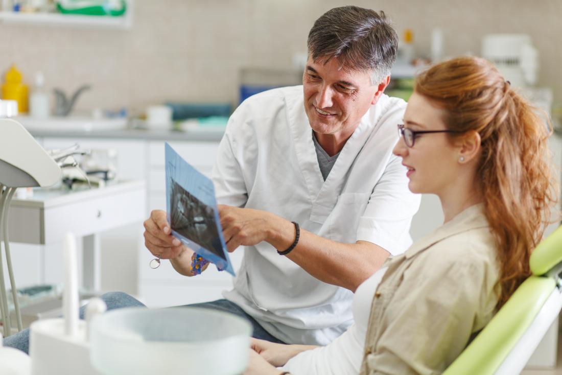 Dentista masculina com paciente do sexo feminino, olhando para um raio-x de seus dentes e gengivas.