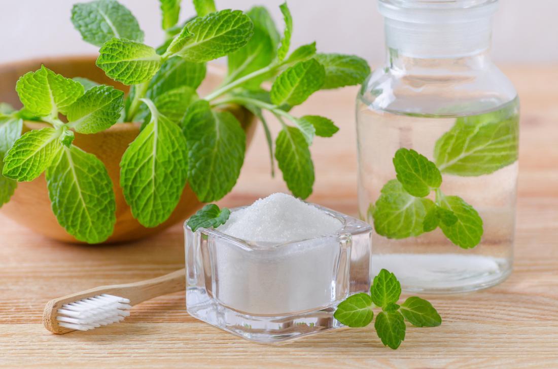 Uma escova de dentes de madeira, planta da hortelã, potenciômetro de vidro do sal, e garrafa de vidro do líquido claro, em uma tabela de madeira. Ingredientes para bochechos naturais sal.
