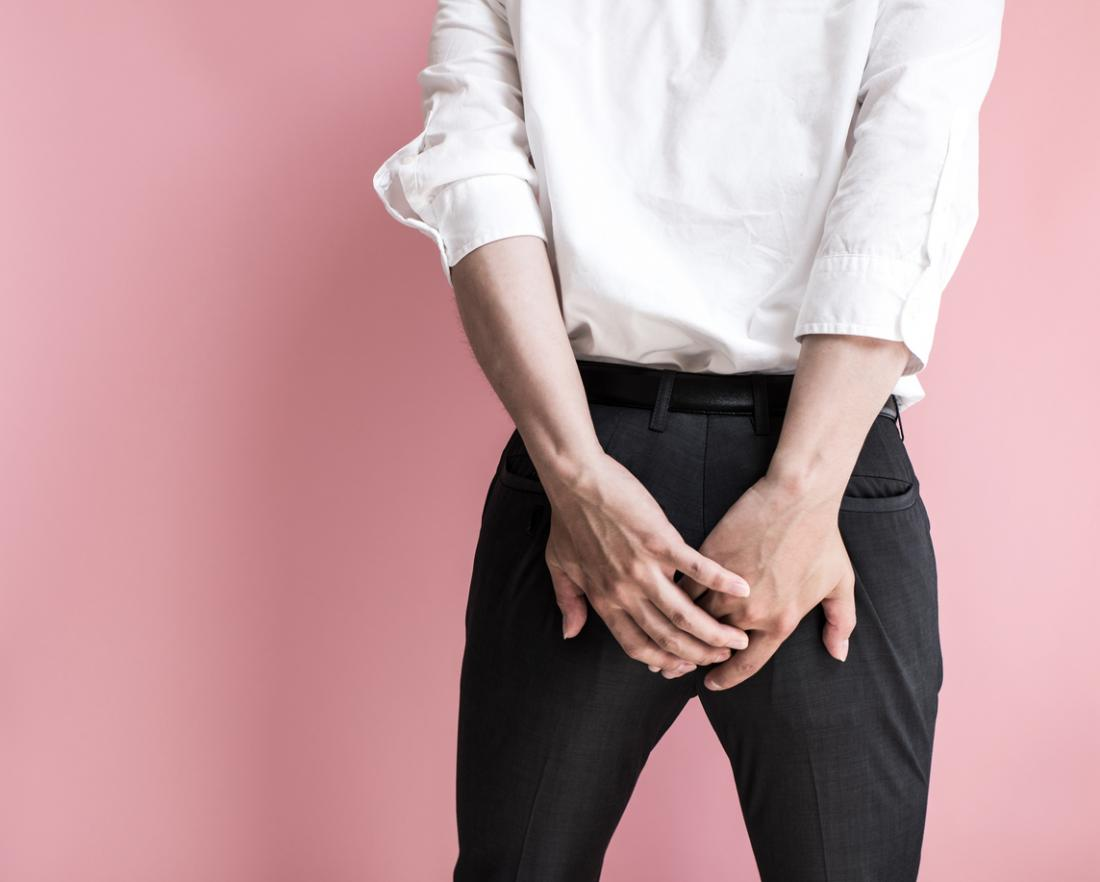 Homem segurando suas nádegas.