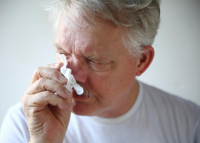 Un vieil homme avec un nez qui coule.