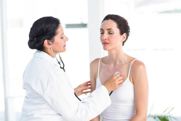 Un médecin examine la poitrine d'une femme.