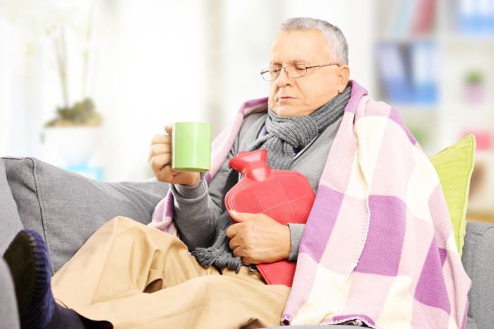 Un vieil homme avec une couverture, une bouteille d'eau chaude et une tasse.