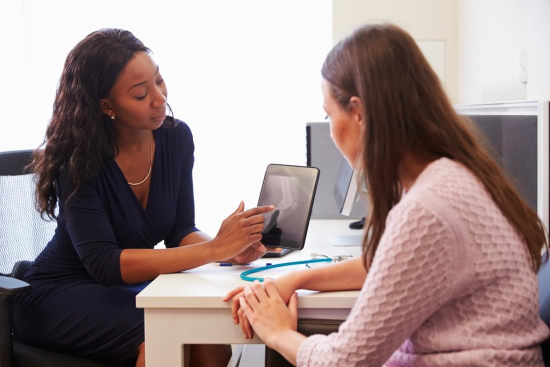 女性の医者と女性の患者は、タブレットを使用して結果を議論します。