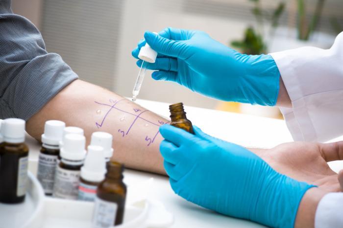 [un médecin fait un test d'allergie sur le bras d'un patient]