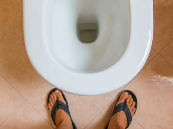 Mann, der über Toilette steht