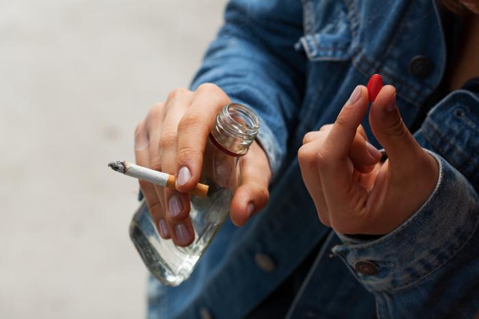 Pessoa bebendo álcool, fumando e tomando drogas