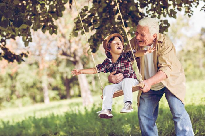 Älterer Mann, der Enkel auf Schwingen drückt