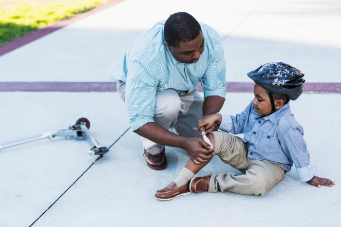 父は彼の息子の裸の膝の上に石膏を置く
