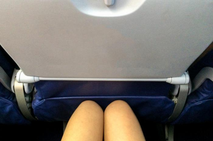 飛行機の前に座っている婦人の膝