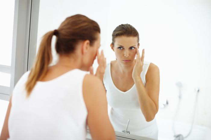 Uma mulher está aplicando loção para os olhos.