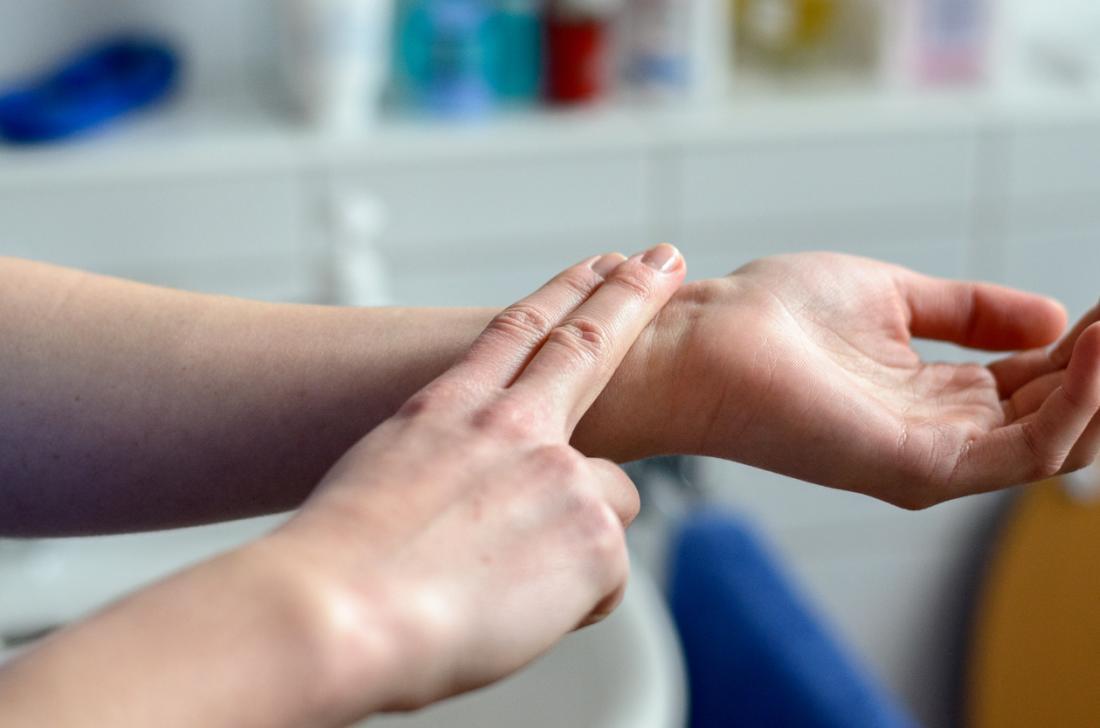 Mulher verificando seu pulso, colocando dois dedos no pulso dela.