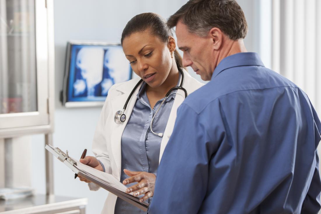 Докторе, гледайки клипборда, говорейки на пациента.