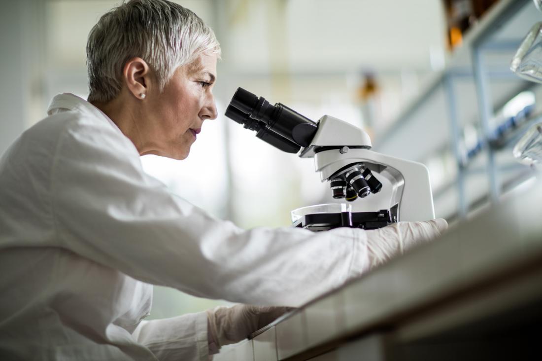 Nhà khoa học nhìn qua kính hiển vi