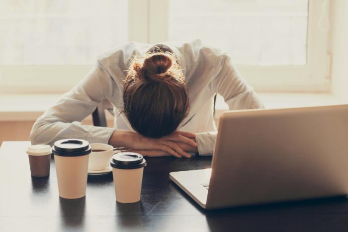 Nhân viên văn phòng buồn ngủ tại bàn làm việc với nhiều loại cà phê.