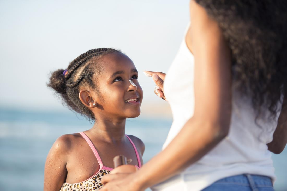 garota na praia com protetor solar no nariz