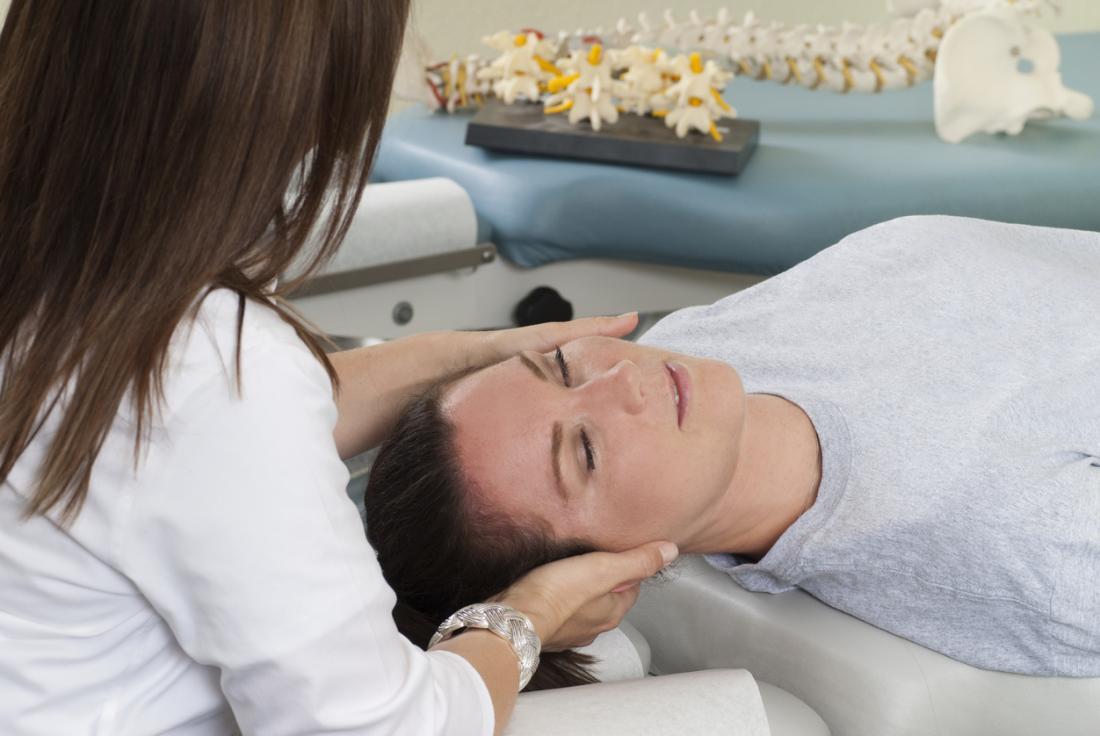 Mulher em quiropráticos tendo uma massagem de cabeça e pescoço.