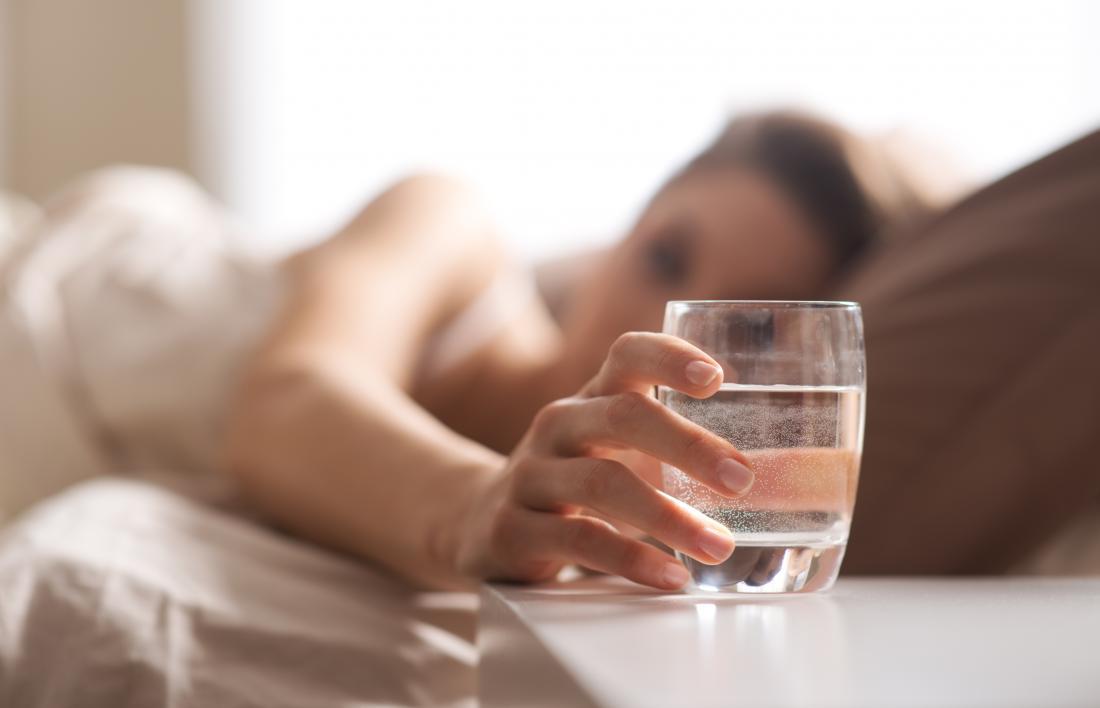 Frau im Bett, das für Glas Wasser erreicht, um vor dem Schlafengehen zu trinken.