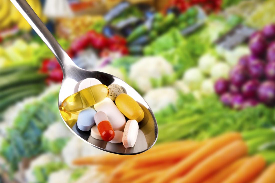 野菜の上にさまざまなビタミンやサプリメントをスプーンします。
