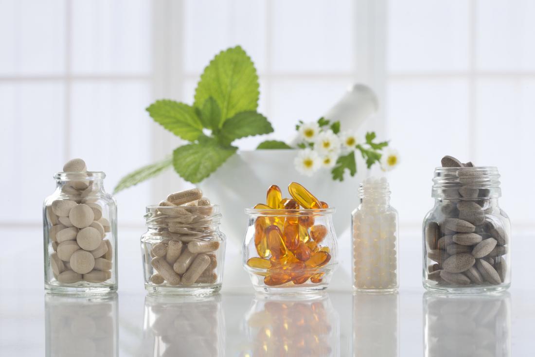 Bouteilles en verre et pots remplis de différentes vitamines et suppléments.