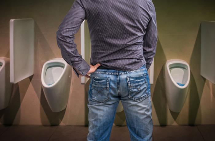 [男はトイレの便器にこぼれ落ちる]